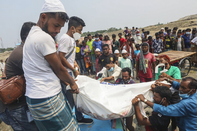 The body of a victim is carried after a speedboat overturned Monday morning after hitting a cargo boat in River Padma at the Kanthalbari ferry terminal in Madaripur, central Bangladesh, Monday, May 3, 2021. More than two dozen people were killed. (AP Photo/Abdul Goni)