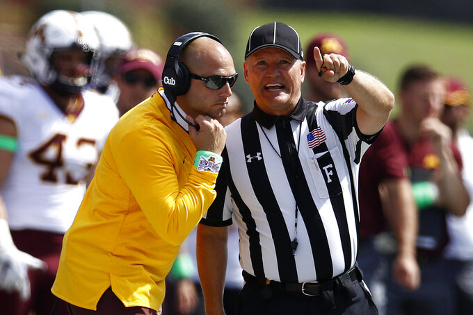 Minnesota head coach P. J. Fleck, left, speaks with an official in the first half of an NCAA college football game against Maryland, Saturday, Sept. 22, 2018, in College Park, Md. (AP Photo/Patrick Semansky)