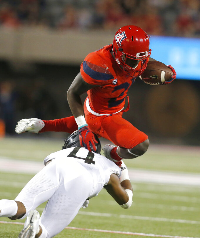 Arizona running back J.J. Taylor leaps over Oregon cornerback Thomas Graham Jr. (4) in the second half during an NCAA college football game, Saturday, Oct. 27, 2018, in Tucson, Ariz. (AP Photo/Rick Scuteri)