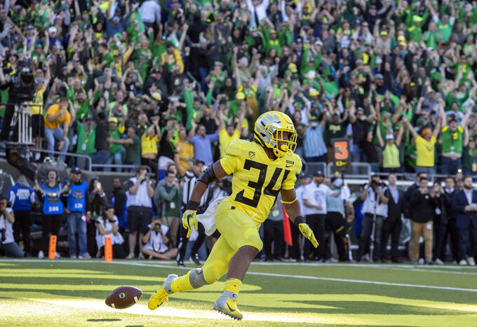 FILE - In this Oct. 13, 2018, file photo, Oregon running back CJ Verdell (34) celebrates after scoring the winning touchdown in overtime to beat Washington 30-27 in an NCAA college football game in Eugene, Ore. There's a pair of running backs in the state of Oregon that are making a case for Freshman of the Year honors: The Beavers' Jermar Jefferson and the Ducks' CJ Verdell. (AP Photo/Thomas Boyd, File)