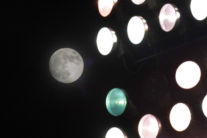 The moon rises behind lights at Kansas Memorial Stadium during the first half of an NCAA college football game between Kansas and TCU in Lawrence, Kan., Saturday, Nov. 28, 2020. (AP Photo/Orlin Wagner)