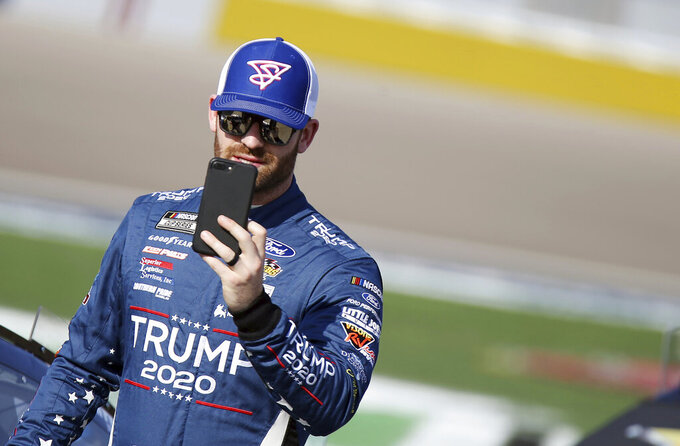 Corey Lajoie uses a phone before a NASCAR Cup Series auto race Sunday, Sept. 27, 2020, in Las Vegas. (AP Photo/Isaac Brekken)