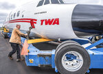 Marty Batura, from Worldwide Aircraft Recovery, checks the rigging on the body of a TWA aircraft, which is being moved to JFK airport to join the TWA Hotel complex as a cocktail bar, at the Auburn-Lewiston Airport in Auburn, Maine, Monday, Oct. 8, 2018. A vintage commercial airplane is set to undertake a long, slow journey from Maine to New York where it will be turned into a cocktail lounge. (Andree Kehn/Sun Journal via AP)