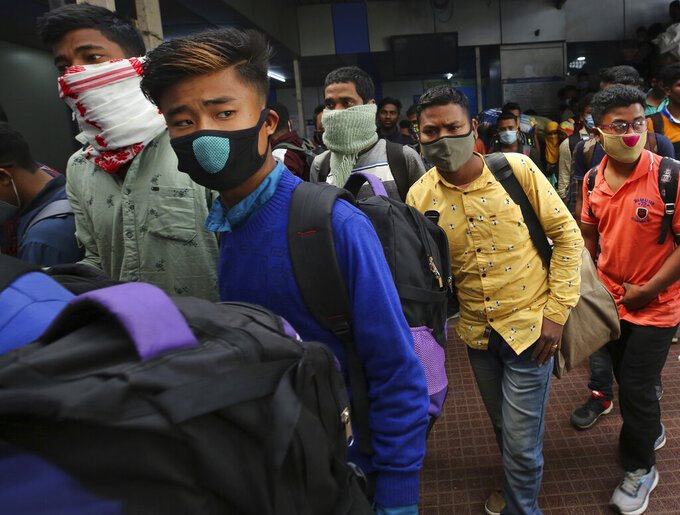 People wearing face masks as a precaution against the coronavirus arrive at a train station in Bengaluru, India, Monday, Feb. 22, 2021. Cases of COVID-19 are increasing in some parts of India after months of a steady nationwide decline, prompting authorities to impose lockdowns and other virus restrictions. (AP Photo/Aijaz Rahi)