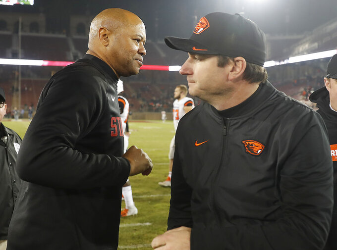 Stanford head coach David Shaw, left, and Oregon State head coach Jonathan Smith, right, shake hands at midfield after an NCAA college football game on Saturday, Nov. 10, 2018, in Stanford, Calif. Stanford won 48-17. (AP Photo/Tony Avelar)