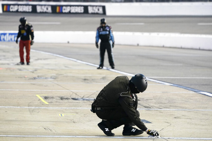 A pit crew member dries the stripe in the pits during a caution during a NASCAR Xfinity Series auto race Friday, Sept. 11, 2020, in Richmond, Va. (AP Photo/Steve Helber)