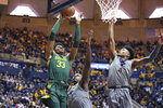 Baylor forward Freddie Gillespie (33) shoots while defended by West Virginia forward Oscar Tshiebwe (34) and guard Miles McBride (4) during the first half of an NCAA college basketball game Saturday, March 7, 2020, in Morgantown, W.Va. (AP Photo/Kathleen Batten)