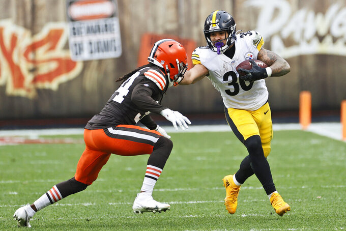 Pittsburgh Steelers running back James Conner (30) tries to avoid a tackle by Cleveland Browns cornerback Robert Jackson (34) during the first half of an NFL football game, Sunday, Jan. 3, 2021, in Cleveland. (AP Photo/Ron Schwane)