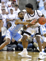 North Carolina guard Seventh Woods (0) attempts to tip the ball away from Louisville guard Darius Perry (2) during the first half of an NCAA college basketball game in Louisville, Ky., Saturday, Feb. 2, 2019. (AP Photo/Timothy D. Easley)