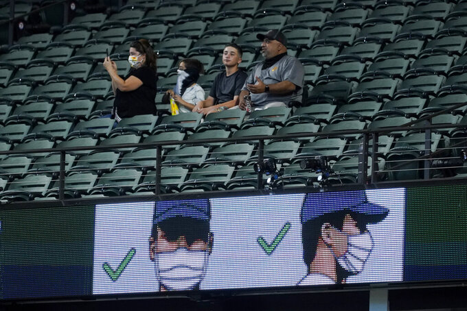 Fans watch during batting practice before Game 1 of a baseball National League Championship Series between the Los Angeles Dodgers and the Atlanta Braves Monday, Oct. 12, 2020, in Arlington, Texas. (AP Photo/Tony Gutierrez)