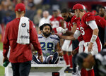 FILE - In this Sept. 30, 2018, file photo, Seattle Seahawks defensive back Earl Thomas (29) is greeted by Arizona Cardinals players as he leaves the field after breaking his leg during the second half of an NFL football game in Glendale, Ariz. Thomas held out through the preseason for a new, cash-up-front, long-term contract in case of a serious injury. Thomas failed to get what he wanted and played instead under his soon-to-expire contract this year until he broke his leg in the fourth game of the season. (AP Photo/Ross D. Franklin, File)