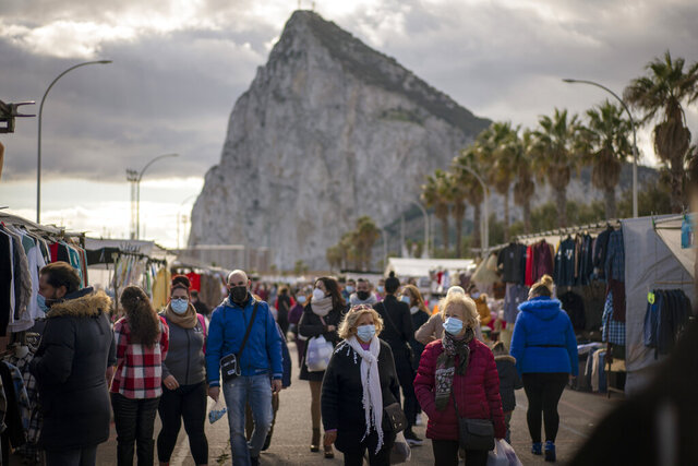 Backdropped by the Gibraltar rock, people walk along the stalls of a weekly market at the Spanish city of La Linea on Monday, Jan. 4, 2021. Fears of disruptions following Britain's departure from the European Union were replaced by coronavirus-related restrictions on border traffic between Spain and Gibraltar on Monday, the first working day at the United Kingdom's only land border with the European mainland. (AP Photo/Emilio Morenatti)