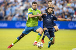 Sporting Kansas City midfielder Graham Zusi knocks the ball away from an attacking Seattle Sounders defender Will Bruin during the first half of an MLS soccer match Sunday, Sept. 26, 2021, in Kansas City, Kan. (AP Photo/Nick Tre. Smith)