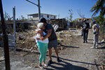 A woman affected by last week's tornado receives a hug from a volunteer who is helping distribute donated items in El Roble, on the outskirts of Havana, Cuba, Wednesday, Feb. 6, 2019. In some areas, individuals began arriving the next day with boxes of rice, water and clothing. In others, private restaurants and bakeries set up stands where they distributed free food day.  (AP Photo/Ramon Espinosa)