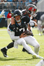Jacksonville Jaguars quarterback Nick Foles, left, is sacked by Tampa Bay Buccaneers linebacker Carl Nassib during the first half of an NFL football game, Sunday, Dec. 1, 2019, in Jacksonville, Fla. (AP Photo/Stephen B. Morton)