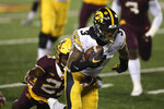 Iowa wide receiver Tyrone Tracy Jr. (3) carries the ball in front of Minnesota defensive back Justus Harris (21) during the first half of an NCAA college football game Friday, Nov. 13, 2020, in Minneapolis. (AP Photo/Stacy Bengs)