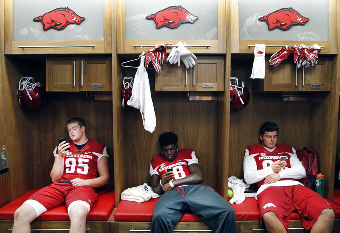 FILE - In this Aug. 9, 2015, file photo, from left to right, Arkansas' Jake Hall, La'Michael Pettway and Karl Roesler pass the time with their cell phones in the players' locker room during the annual NCAA college football media day event in Fayetteville, Ark. While autograph-signing and public appearances have been traditional ways athletes could make extra money, opportunities now are tied to social media posts where athletes could in the future be paid be paid for posting sponsored content. (AP Photo/Samantha Baker, File)