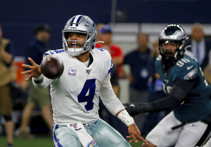 Dallas Cowboys' Dak Prescott (4) pitches the ball out to Tavon Austin under pressure from Philadelphia Eagles' Derek Barnett (96) in the first half of an NFL football game in Arlington, Texas, Oct. 20, 2019. (AP Photo/Michael Ainsworth)