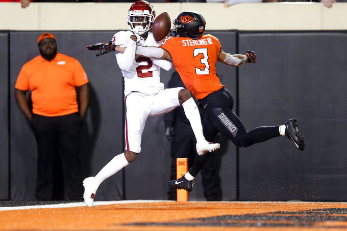 Oklahoma wide receiver CeeDee Lamb (2) attempts to make a catch in the end zone while being defended by Oklahoma State safety Tre Sterling (3) during an NCAA college football game, Saturday, Nov. 30, 2019, in Stillwater, Okla. (Ian Maule/Tulsa World via AP)
