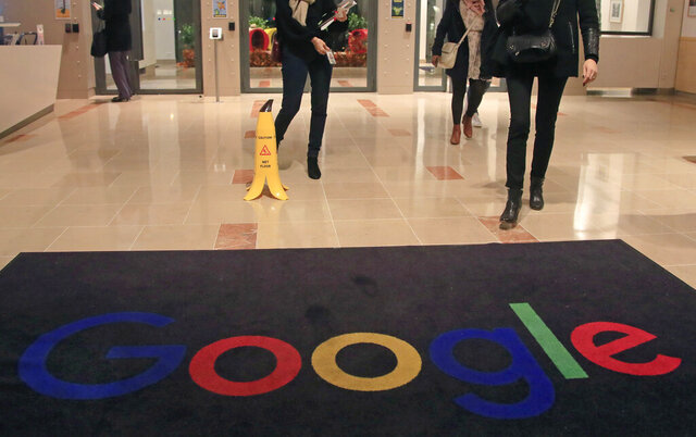 """FILE - In this file photo dated Nov. 18, 2019, Google employees walks out of Google France building in Paris. France.  France's highest administrative court on Friday June 19, 2020, has upheld a fine of 50 million euros (dollars 56 million US) against Google for not being """"sufficiently clear and transparent"""" with users of Android about their data protection options. (AP Photo/Michel Euler, File)"""