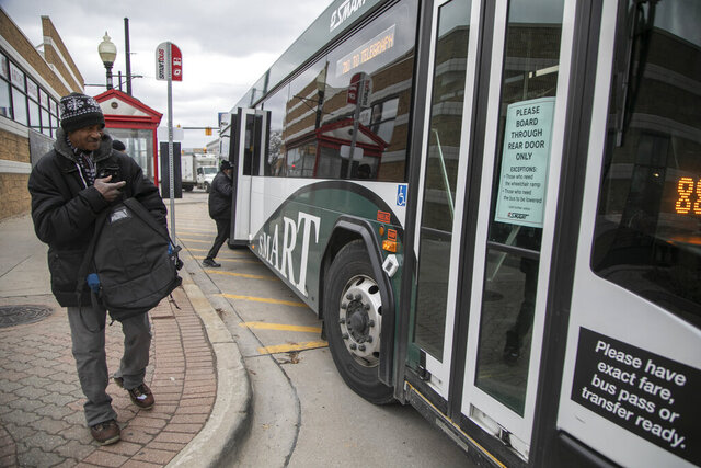 A man unknowingly attempted to board his SMART bus at 9 Mile and Woodward in Ferndale, Mich., from the front Tuesday, March, 17, 2020. Passengers have been requested to enter from the back of the busses due to Coronavirus threat. (Mandi Wright/Detroit Free Press via AP)