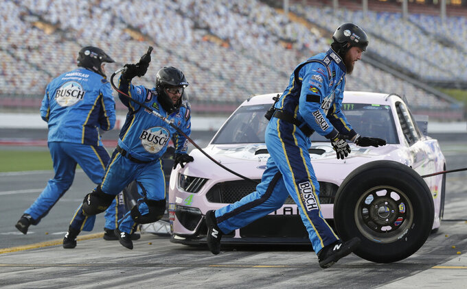 Crew members perform a pit stop on driver Kevin Harvick's car during qualifying for Saturday's NASCAR All-Star Cup series auto race at Charlotte Motor Speedway in Concord, N.C., Friday, May 17, 2019. (AP Photo/Chuck Burton)