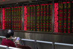 In this Thursday, Jan. 16, 2020, photo, an investor monitors stock prices at a brokerage in Beijing. Asian stock markets on Friday, Jan. 17 have followed Wall Street higher after China reported its economy grew by 6.1% in 2019 and Washington and Beijing signed an interim trade agreement. (AP Photo/Ng Han Guan)