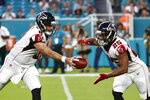 Atlanta Falcons quarterback Matt Schaub (8) hands off to running back Ito Smith (25) during the first half of a preseason NFL football game against the Miami Dolphins, Thursday, Aug. 8, 2019, in Miami Gardens, Fla. (AP Photo/Brynn Anderson)