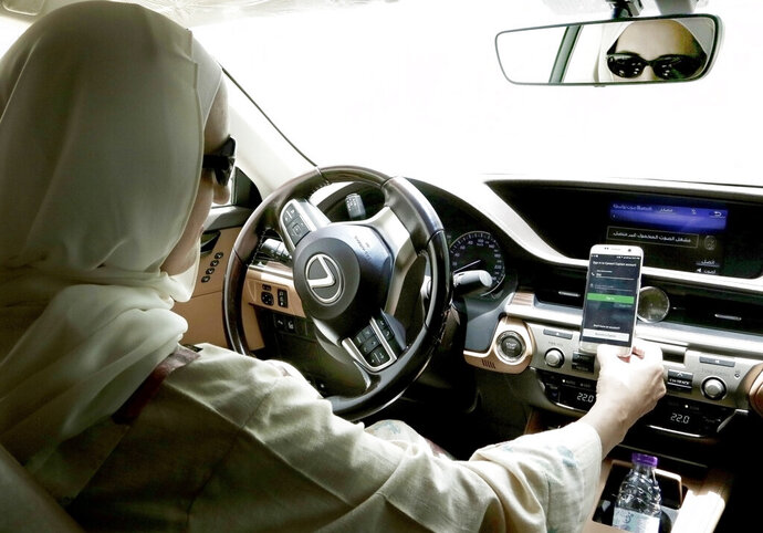 In this June 24, 2018 photo, Ammal Farahat, who has signed up to be a driver for Careem, a regional ride-hailing service that is a competitor to Uber, opens the Careem app on her mobile phone before she starts driving, in Riyadh, Saudi Arabia. Ride-hailing service Uber announced on Tuesday, March 26, 2019 it has acquired Mideast competitor Careem for $3.1 billion, giving the San Francisco-based firm the commanding edge in a region with a large young, tech-savvy population. (AP Photo/Nariman El-Mofty)