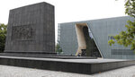 People pass the Museum of the History of Polish Jews 'POLIN' in Warsaw, Poland, Tuesday, 16 July 2019. A Jewish association has said that some private donors to Poland's renowned Jewish history museum have suspended their donations out of concern over the government's failure to extend the term of its director. (AP Photo/Czarek Sokolowski)