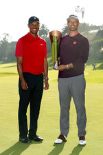 Adam Scott, right, of Australia, poses with his trophy next to Tiger Woods on the 18th green after winning the Genesis Invitational golf tournament at Riviera Country Club, Sunday, Feb. 16, 2020, in the Pacific Palisades area of Los Angeles. (AP Photo/Ryan Kang)