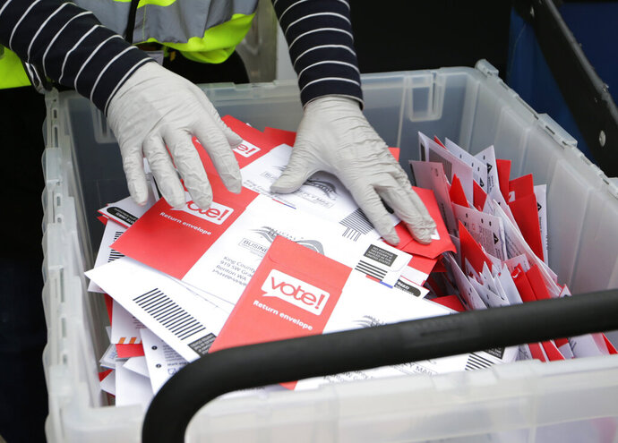 FILE - In this March 10, 2020, file photo wearing gloves, a King County Election worker collect ballots from a drop box in the Washington State primary, in Seattle. But the 2020 presidential election is creeping ever closer, and there are no signs yet of pandemic abating, nor any word on when Americans on orders to stay home can resume normal life, and so lawmakers are trying to figure how to allow for voting in a world where face-to-face contact causes anxiety at the least, and sickness and death at the most. (AP Photo/John Froschauer, File)