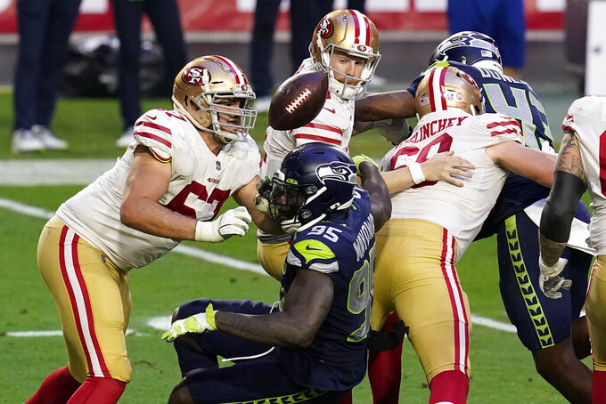 San Francisco 49ers quarterback C.J. Beathard fumbles the ball as Seattle Seahawks defensive end Benson Mayowa (95) defends during the second half of an NFL football game, Sunday, Jan. 3, 2021, in Glendale, Ariz. (AP Photo/Ross D. Franklin)