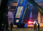 A bus in New York City which careened off a road in the Bronx neighborhood of New York and is left dangling from an overpass Friday, Jan. 15, 2021, after a crash late Thursday that left the driver in serious condition, police said. (AP Photo/Craig Ruttle)