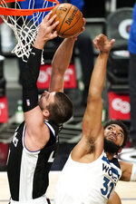 Los Angeles Clippers center Ivica Zubac, left, grabs a rebound away from Minnesota Timberwolves center Karl-Anthony Towns during the first half of an NBA basketball game Sunday, April 18, 2021, in Los Angeles. (AP Photo/Mark J. Terrill)