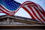 FILE - In this March 22, 2019 file photo, an American flag flies outside the Department of Justice in Washington. The FBI, in a change of policy, is committing to inform state officials if local election systems have been breached, federal officials told The Associated Press. (AP Photo/Andrew Harnik)