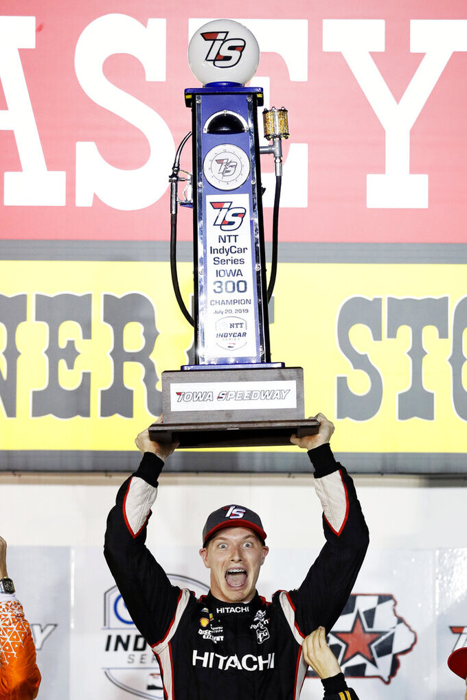 Josef Newgarden celebrates with the trophy after winning the IndyCar Series auto race Sunday, July 21, 2019, at Iowa Speedway in Newton, Iowa. (AP Photo/Charlie Neibergall)