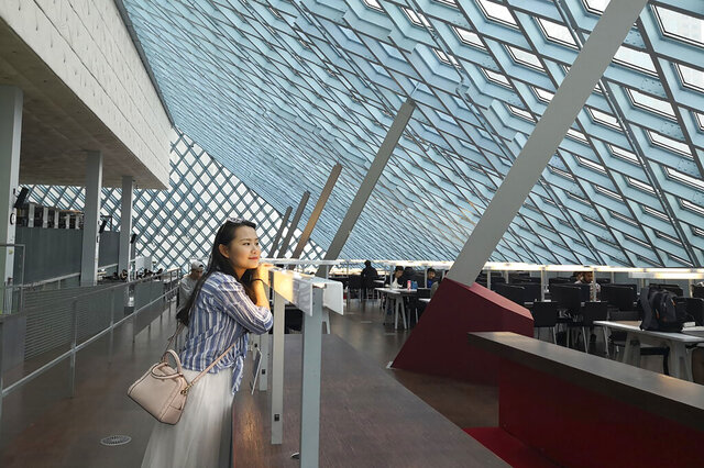 In this August 2019, photo released by Florian Hayek, Courtney Huang, a Chinese citizen living and working in the United States, poses for a photo in the Central Library in Seattle, Wa. Huang is one of hundreds of Chinese whose jobs, lives, and right to work in the U.S. are on the line after the Trump administration imposed a travel ban and visa processing halt on foreigners in China over the coronavirus outbreak. Huang, who aspires to become a U.S. citizen, is worried that she could lose her job and her right to live in the States because her work visa wasn't issued due to the halt. (Florian Hayek via AP)