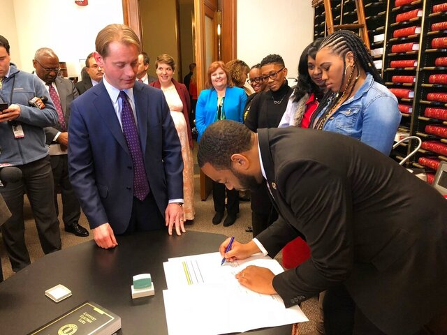 Kentucky state Rep. Charles Booker, right, officially files on Wednesday, Jan. 8, 2020, in Frankfort, Ky., to run for the U.S. Senate seat held by Republican Senate Majority Leader Mitch McConnell. Booker joins a crowded field of Democrats competing to challenge McConnell in this year's election. (AP Photo/Bruce Schreiner)