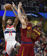 Washington Wizards' Kelly Oubre Jr. (12) shoots over Cleveland Cavaliers' Larry Nance Jr. (22) and Jalen Jones (21) during the second half of an NBA basketball game, Saturday, Dec. 8, 2018, in Cleveland. The Cavaliers won 116-101. (AP Photo/Tony Dejak)