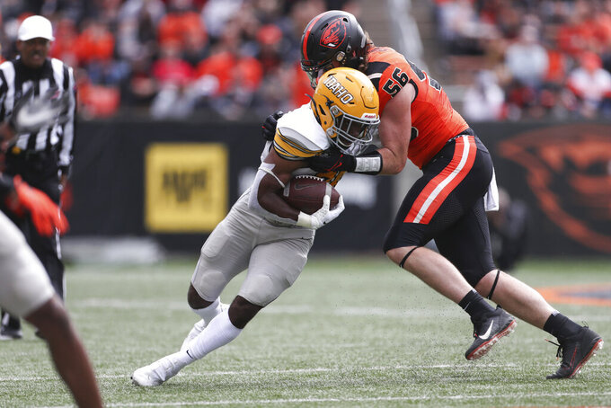 Idaho running back Elisha Cummings (20) is brought down by Oregon State outside linebacker Riley Sharp (56) during the first half of an NCAA college football game Saturday, Sept. 18, 2021, in Corvallis, Ore. (AP Photo/Amanda Loman)