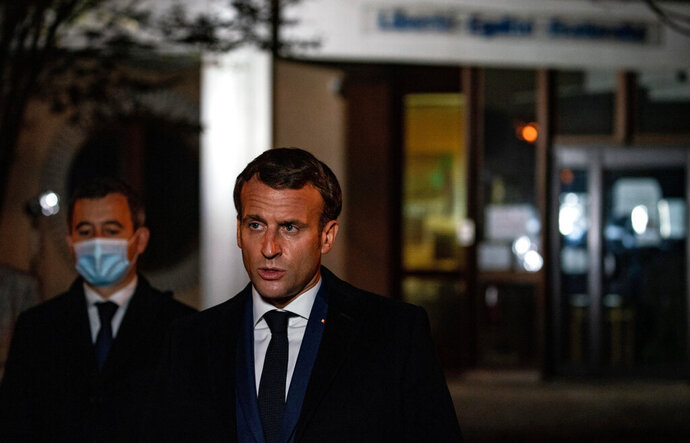 French President Emmanuel Macron speaks in front of a high school Friday Oct.16, 2020 in Conflans Sainte-Honorine, northwest of Paris, where a history teacher who opened a discussion with high school students on caricatures of Islam's Prophet Muhammad was beheaded. French President Emmanuel Macron denounced what he called an