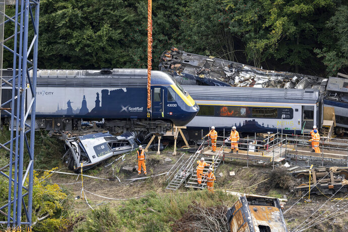 """A carriage is lifted by crane from the site of the Stonehaven rail crash as work continues at the scene in Aberdeenshire, following the derailment of the ScotRail train on Aug. 12 which cost the lives of three people, in Stonehaven, Scotland, Thursday Sept. 10, 2020. An investigation into a train crash in Scotland last month that killed three people has found that the train """"struck a pile of washed-out rock and gravel before derailing."""" In the interim report, Network Rail said the industry needed to learn how to respond better in the future to severe weather. (Derek Ironside/Newsline Media/PA via AP)"""