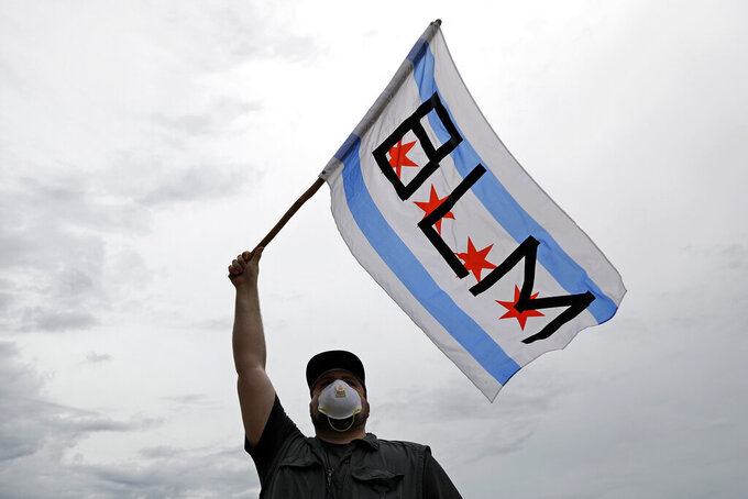 FILE - In this June 3, 2020, file photo, a protester waves a city of Chicago flag emblazoned with the acronym BLM for Black Lives Matter, outside the Batavia, Ill., City Hall during a protest over the death of George Floyd. Black Lives Matter has gone mainstream — and black activists are carefully assessing how they should respond. (AP Photo/Nam Y. Huh, File)