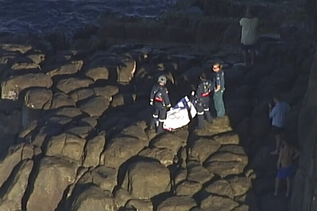 In this image from a video, the covered body is placed on a cliff near Indian Head, Australia Saturday, July 4, 2020. A 20-year-old scuba diver died Saturday after being attacked by a shark off the coast of Australia's Queensland state, authorities said. (AuBC/CHANNEL 7/CHANNEL 9 via AP)
