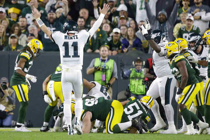 Philadelphia Eagles quarterback Carson Wentz celebrates a touchdown by running back Jordan Howard during the second half of the team's NFL football game against the Green Bay Packers on Thursday, Sept. 26, 2019, in Green Bay, Wis. (AP Photo/Jeffrey Phelps)