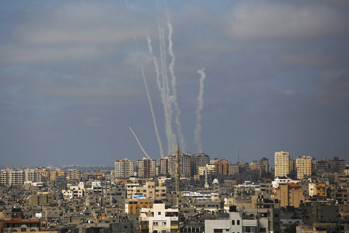 """FILE - In this May 20, 2021 file photo, rockets are launched from the Gaza Strip towards Israel, in Gaza City,  Human Rights Watch said Thursday, Aug. 12, 2021, that the thousands of rockets fired by the Palestinian militant group Hamas during the 11-day war with Israel in May """"violated the laws of war and amount to war crimes."""" The New York-based group said that it investigated Hamas rocket attacks that killed 12 civilians in Israel, as well as a misfired rocket that killed seven Palestinians inside the Gaza Strip. (AP Photo/Hatem Moussa, File)"""