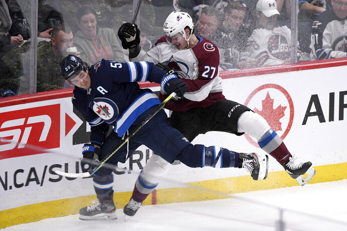 Winnipeg Jets' Mark Scheifele (55) is checked by Colorado Avalanche's Ryan Graves (27) during first period NHL hockey action in Winnipeg, Manitoba Tuesday, Nov. 12, 2019. (Fred Greenslade/The Canadian Press via AP)