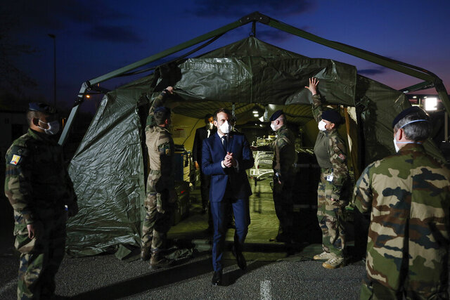French President Emmanuel Macron wears a face mask during his visit at the military field hospital in Mulhouse, eastern France, Wednesday, March 25, 2020. French President Emmanuel Macron launched a special military operation Wednesday to help fight the new virus in one of the world's hardest-hit countries. The new coronavirus causes mild or moderate symptoms for most people, but for some, especially older adults and people with existing health problems, it can cause more severe illness or death. (Mathieu Cugnot/Pool via AP)