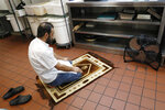 In this Wednesday, Oct. 9, 2019, photo, with shoes removed as is customary, Syrian refugee chef Diaa Alhanoun prays on a carpet facing Mecca in the basement kitchen of Sakib, his Williamsburg, Brooklyn restaurant, in New York. An observant Muslim Alhanoun prays up to five times a day, observing the ritual movements and as his religion requires. (AP Photo/Kathy Willens)